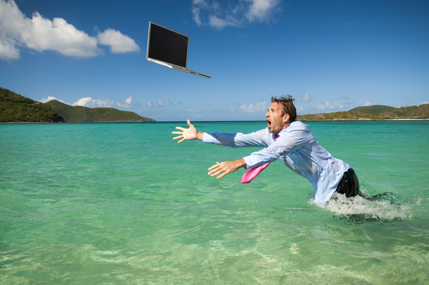 Helpless businessman leaping out of the water to save his laptop falling sea