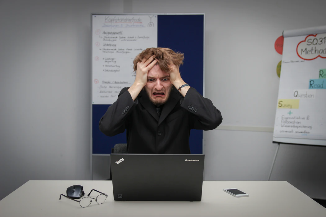 A stressed man looks at his laptop with a panicked expression